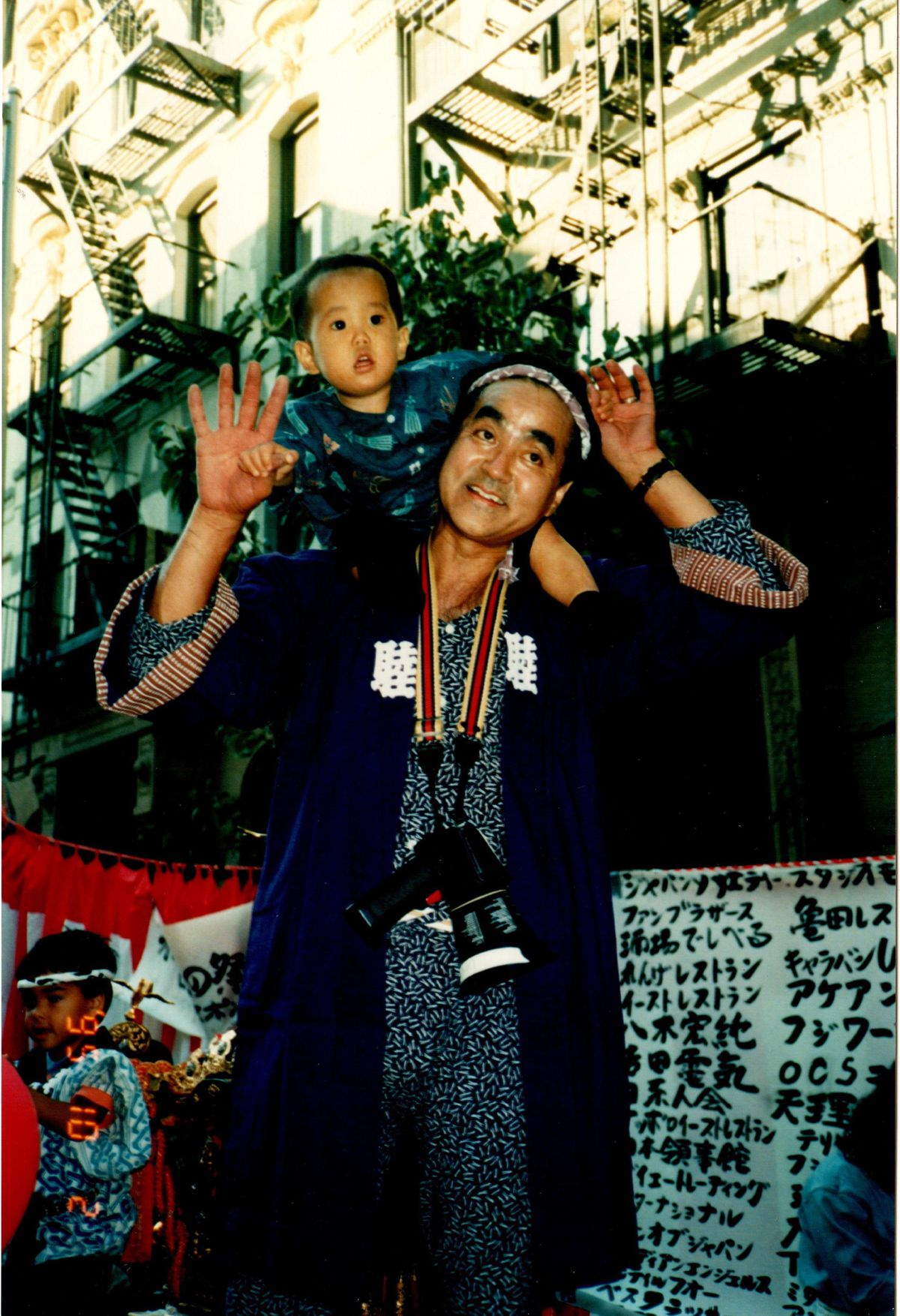 Bon Yagi has his arms up, with his baby son sitting on his shoulders.