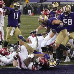 Utah running back Devin Brumfield, lower left, rushes for a touchdown against Washington during the first half of an NCAA college football game Saturday, Nov. 28, 2020, in Seattle.