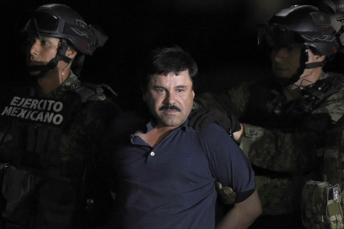 El Chapo is escorted by Mexican marines into a helicopter at Mexico City's airport.