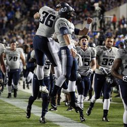 Utah State players celebrate during the first half with a lead over BYU during NCAA football in Provo, Friday, Oct. 3, 2014.