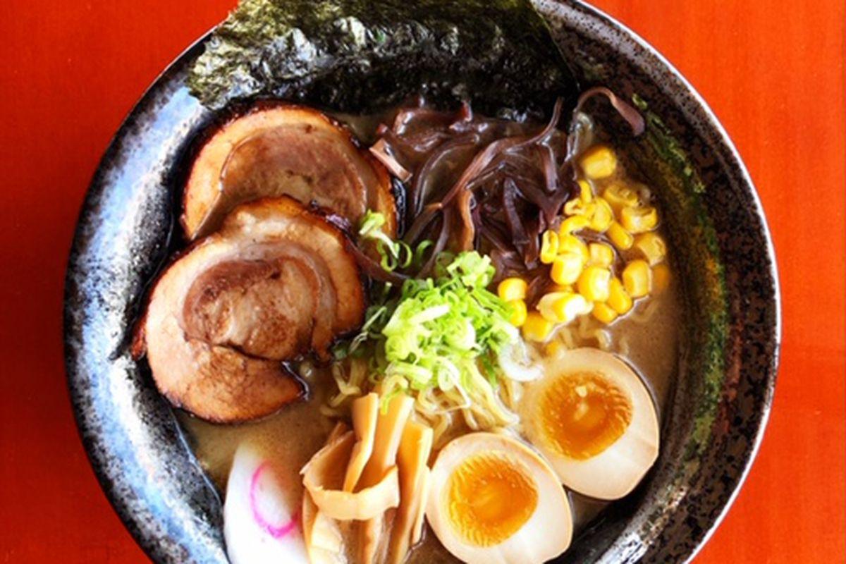 Ramen topped with fish cake, egg, chashu, corn, green onion