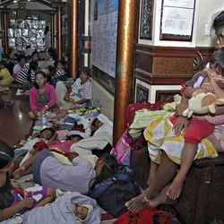 Residents take shelter at the lobby of the city hall in Tandag, Surigao Del Sur province in southern Philippines, Friday, Aug. 31, 2012, following a 7.6 magnitude earthquake that struck eastern and southern Philippines. The quake set off car alarms, shook items off shelves and sent many coastal residents fleeing for high ground before the Pacific Tsunami Warning Center lifted all tsunami alerts it had issued for the Philippines and neighboring countries from Indonesia to Japan, and for Pacific islands as far away as the Northern Marianas.