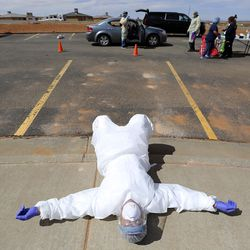 Andy Byrnes, a contracted emergency medical technician with the Utah Department of Health, rests on the sidewalk near the end of a second day of testing for COVID-19 outside of the Monument Valley Health Center in Oljato-Monument Valley, San Juan County, on Friday, April 17, 2020. The mobile testing team tested 1,060 people in two days.
