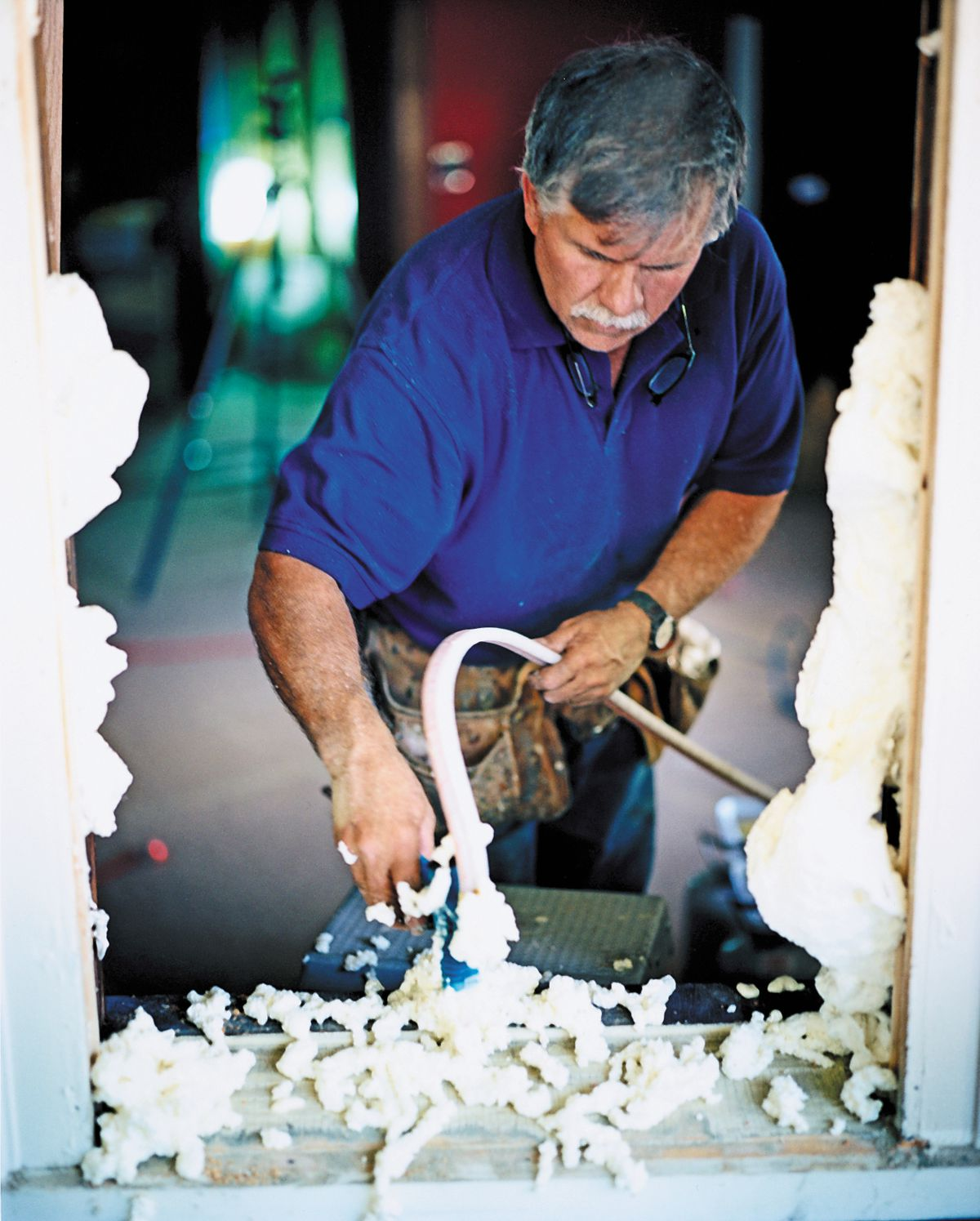 Man Sprays Foam Into Drilled Holes For Window Replacement Preparation