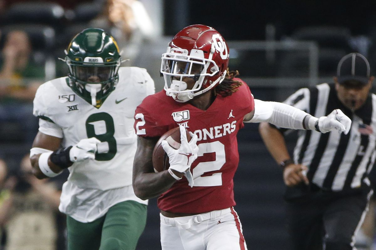 CeeDee Lamb of the Oklahoma Sooners mangages to stay in bounds after catching a pass as Baylor defenders Chris Miller #3 and Henry Black pursue in the first quarter of the Big 12 Football Championship at AT&T Stadium on December 7, 2019 in Arlington, Texas.
