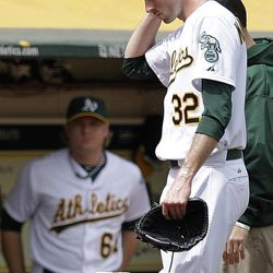 """In this photo from Wednesday, Sept. 5, 2012, Oakland Athletics pitcher Brandon McCarthy (32) places his hand to his head as he leaves the baseball game against the Los Angeles Angels in Oakland, Calif. McCarthy remains in a ''life-threatening'' situation in a Bay Area hospital two days after being hit in the head by a line drive. Struck on the right side of his head by a hard shot from the Angels' Erick Aybar, McCarthy suffered an epidural hemorrhage, brain contusion and skull fracture. He had two hours of surgery to relieve pressure on his brain late Wednesday night. A's athletic trainer Nick Paparesta was asked Friday if McCarthy was still in a life-threatening situation. """"Absolutely he is. It's brain surgery,'' Paparesta said. ''It's life-threatening. At any possible moment something could go wrong, he could have a complication. Absolutely.''"""