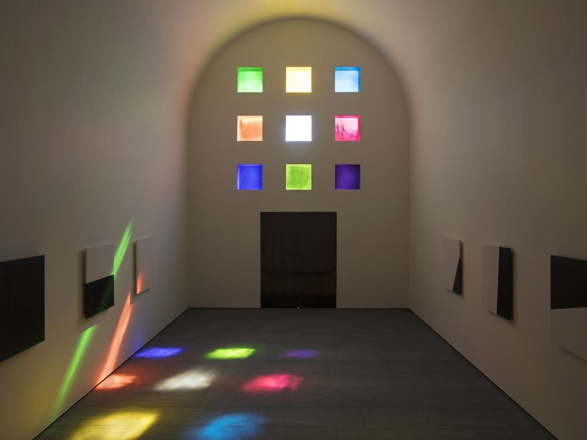 Vaulted stone room with colored glass panels and sun shining through them