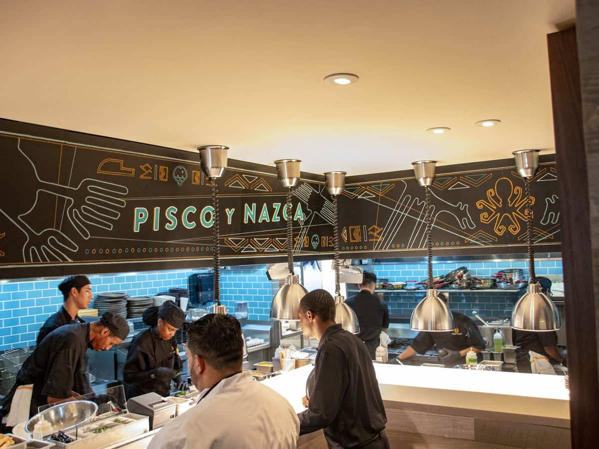 The chef's counter at Pisco y Nazca, with a brick backdrop, blue back lighting and cooks at work