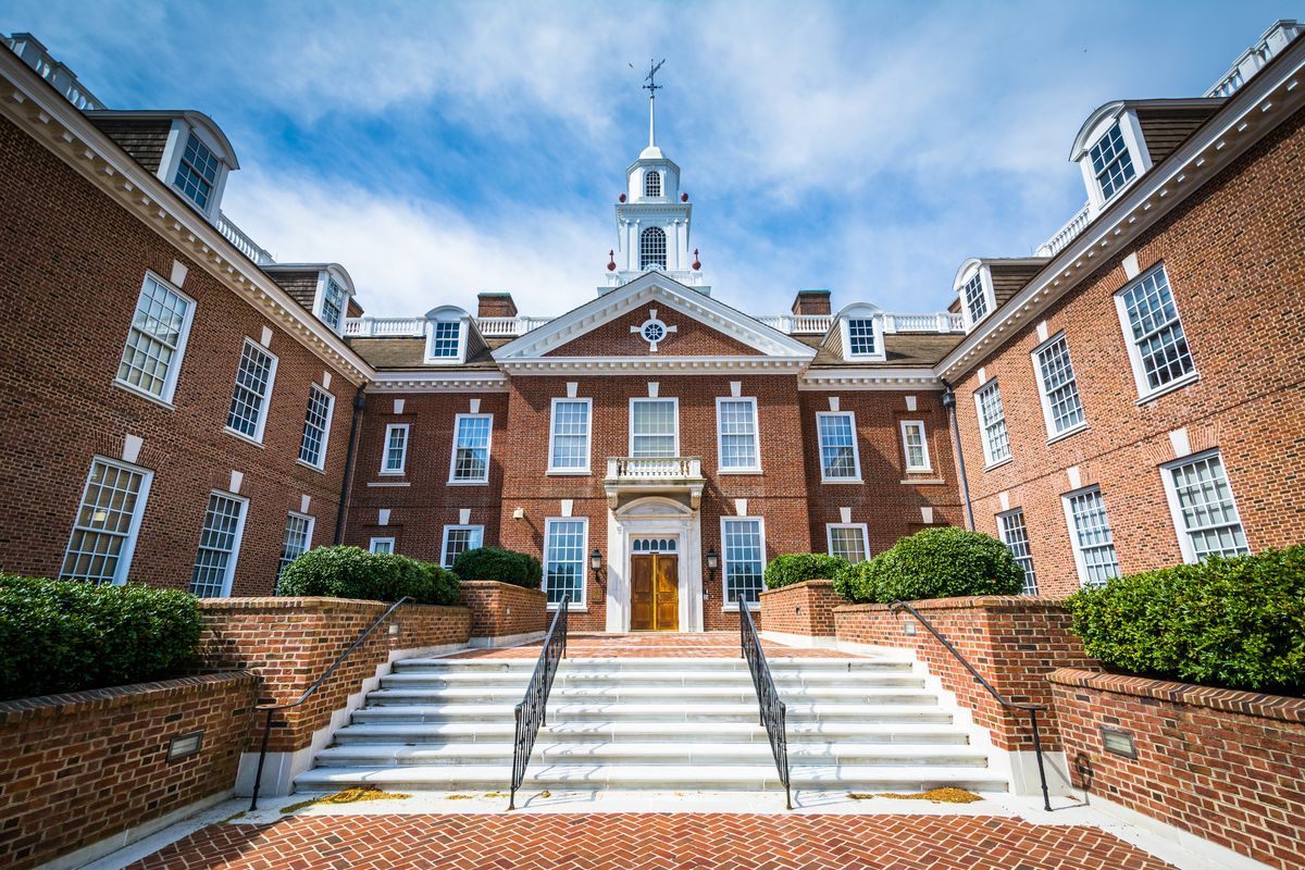 The exterior of the Delaware State Capitol. The facade is red brick. There is a small tower which is white. There are stairs leading up to a brown wooden door.