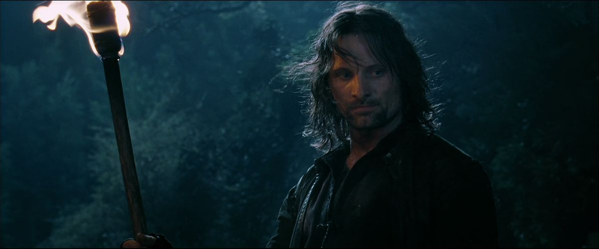 Aragorn holding a torch in a forest in The Fellowship of the Ring.
