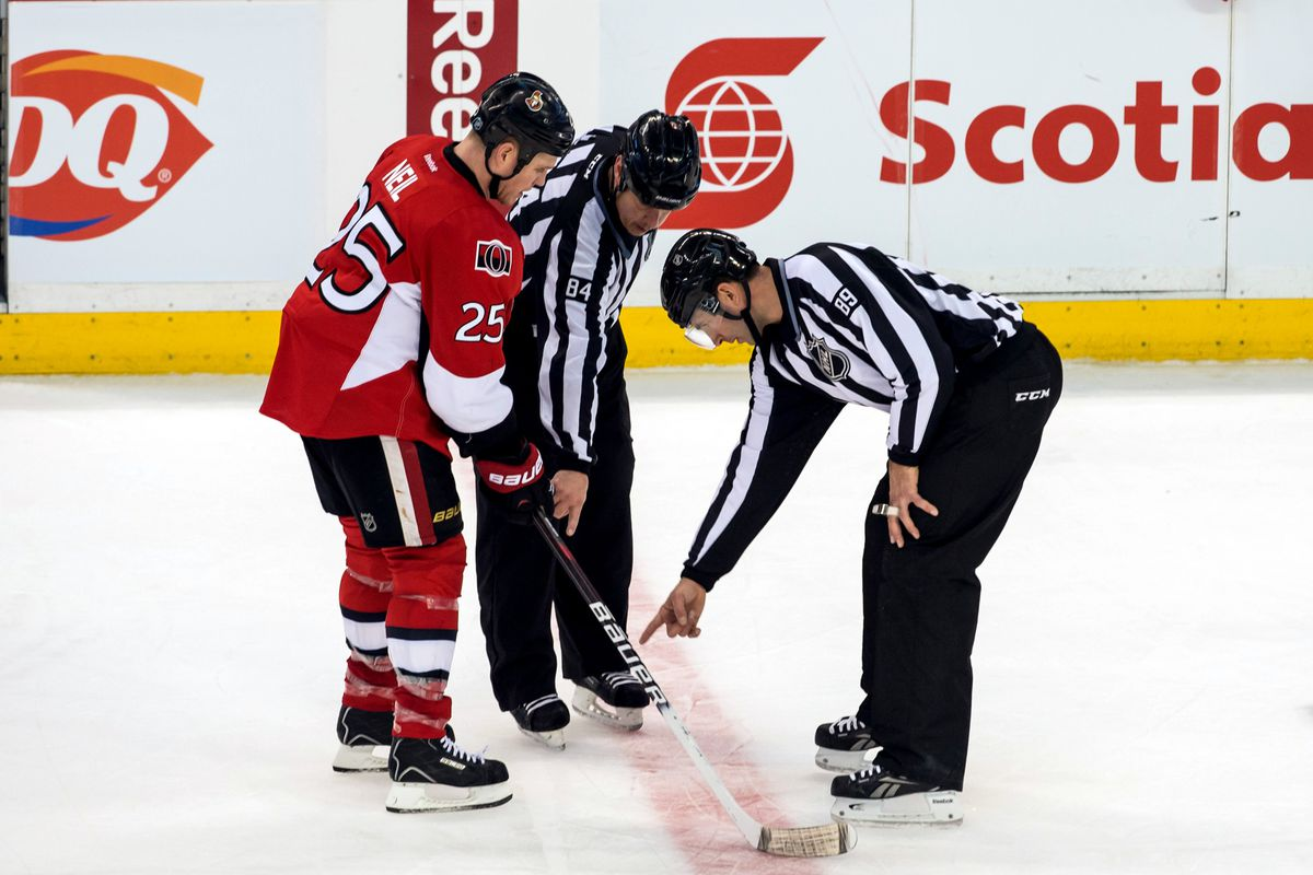 Linesmen attempt to explain the intricacies of the ice surface to Chris Neil