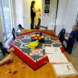 6-year-old Porter Burton, left, plays with toys as mom Mary puts 8-year-old Mykenzie's hair in a ponytail and 3-year-old Logan, right, runs around the house Sept. 25.
