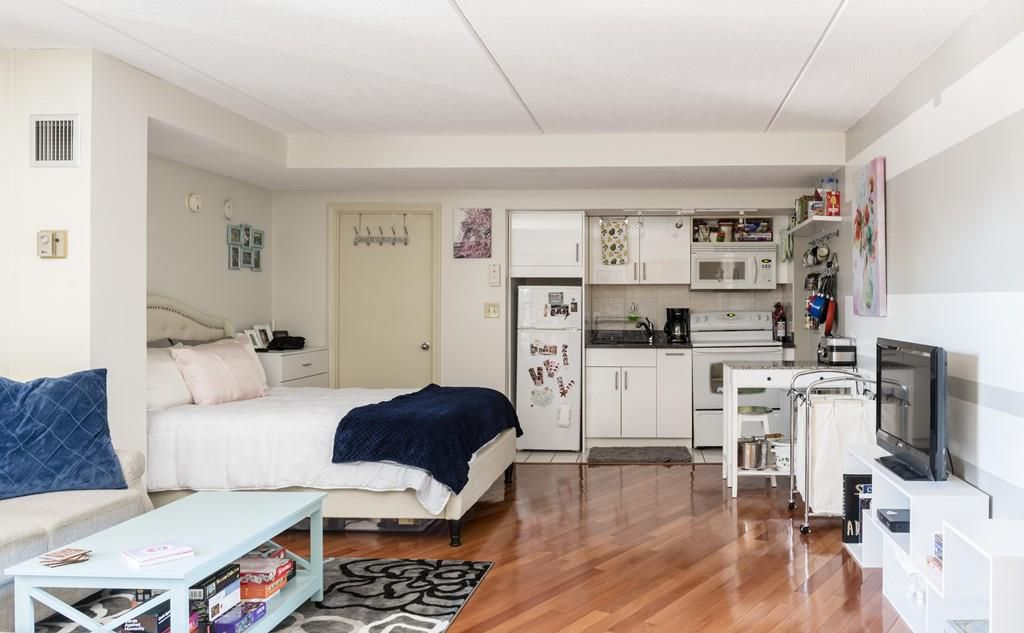 A spacious studio apartment with a bed and a kitchen at one end.