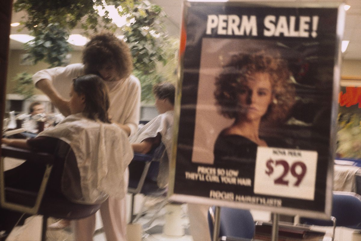 A sign for a perm sale outside a salon at a mall