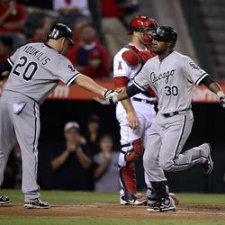 Chicago White Sox's Alejandro De Aza, right, is congratulated by Kevin Youkilis  after hitting a solo home run during the first inning of their baseball game, Friday, Sept. 21, 2012, in Anaheim, Calif.  Los Angeles Angels catcher Chris Iannetta  is at center.
