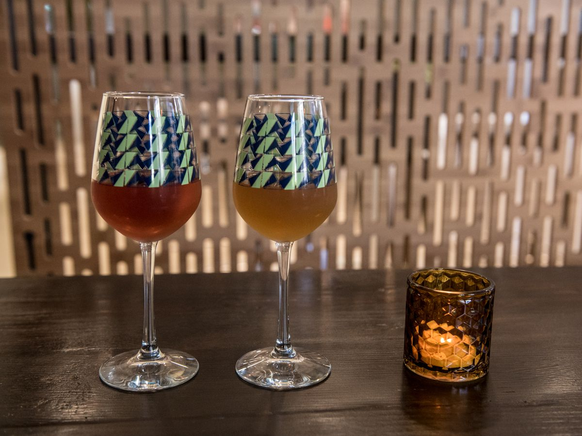 Two glasses of wine on a bar: one red, one orange.