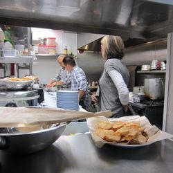 Chef Joshua Clark, back, and his team work on the dishes for the ChowDownTown.