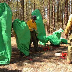 In this April 12, 2012 photo provided by the Cronkite News, Granite Mountain Hotshots crew members train on setting up emergency fire shelters outside of Prescott, Ariz. On Sunday, June 30, 2013, 19 members of the Prescott-based crew were killed in the deadliest wildfire involving firefighters in the U.S. for at least 30 years. The firefighters were forced to deploy their emergency fire shelters - tent-like structures meant to shield firefighters from flames and heat - when they were caught near the central Arizona town of Yarnell, according to a state forestry spokesman. (AP Photo/Cronkite News, Connor Radnovich)