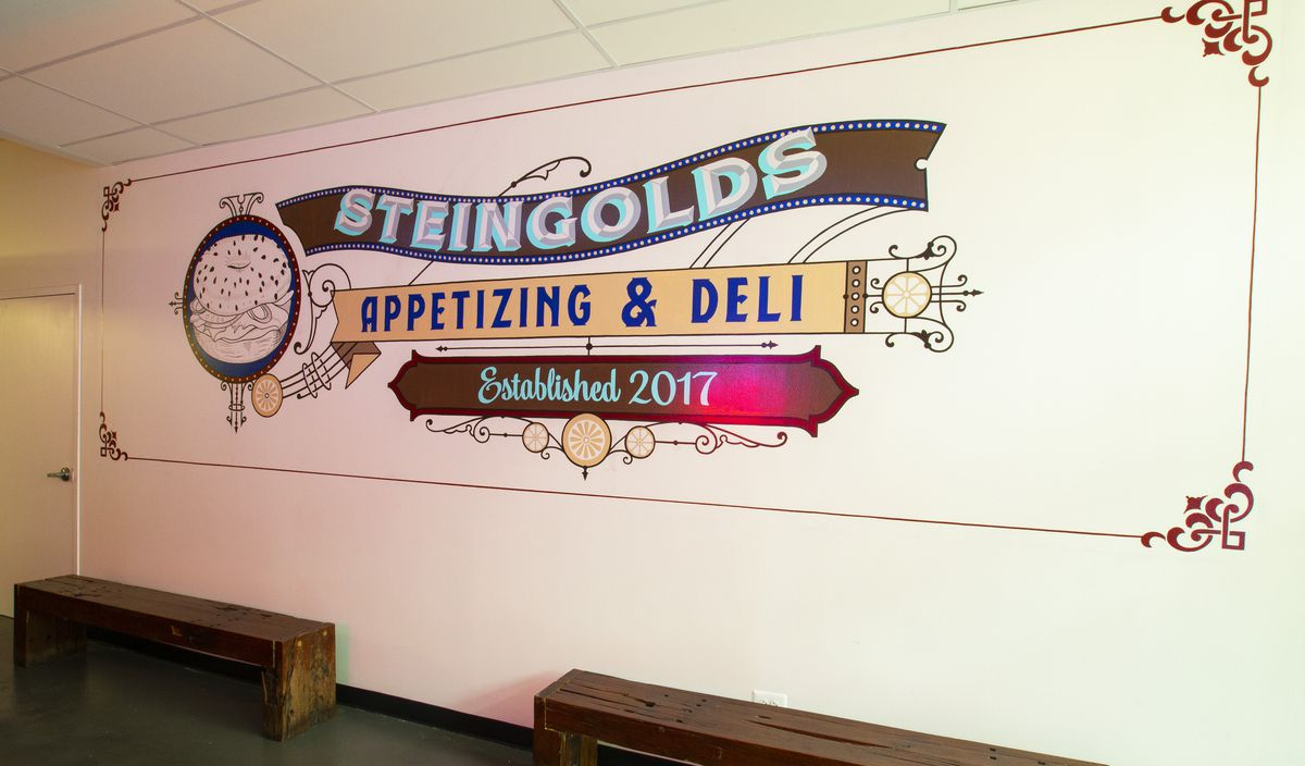 """A large mural on a white wall that reads """"Steingold's Appetizing & Deli, Established 2017"""""""