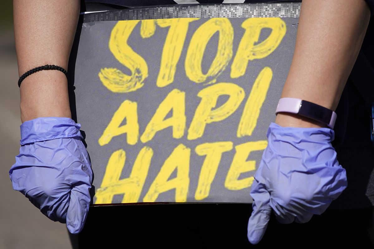In this March 20, 2021, file photo, woman holds a sign and attends a rally to support stop AAPI (Asian Americans and Pacific Islanders) hate at the Logan Square Monument in Chicago.