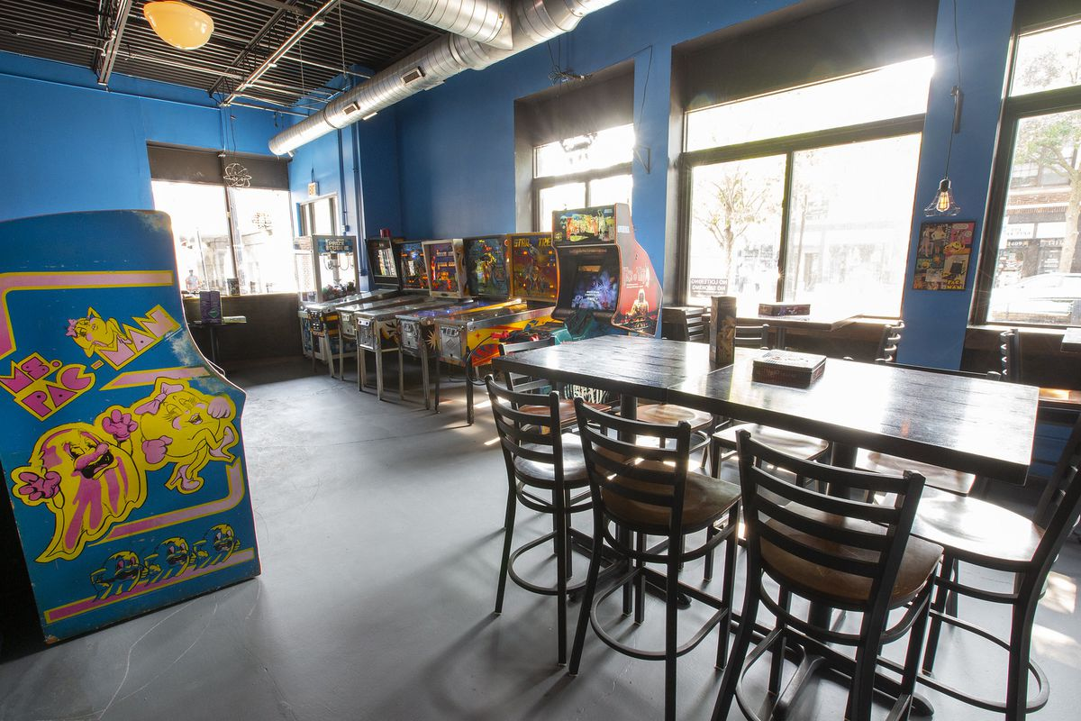 tables, pinball machines, and a ms. pac-man arcade game