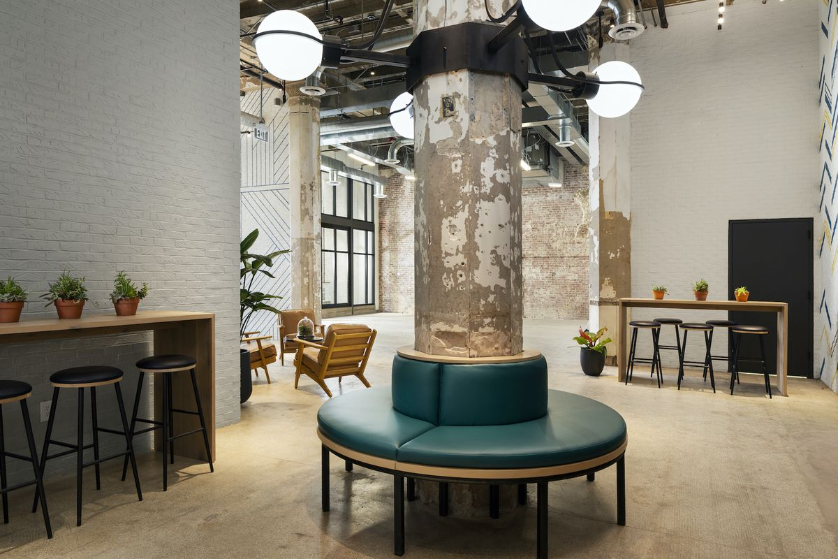 An aging concrete column is wrapped in a new seating option, surrounded by historic hardwood floors in the century-old building.