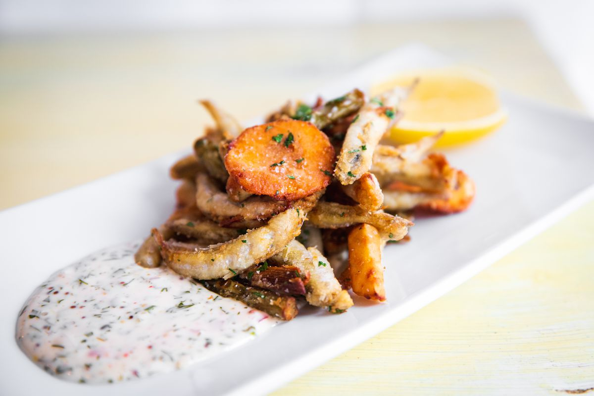 A pile of small fried fish on a white plate