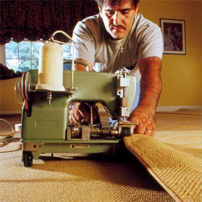 Man Binds Edges Of Carpet With Binding Machine Below Stairs