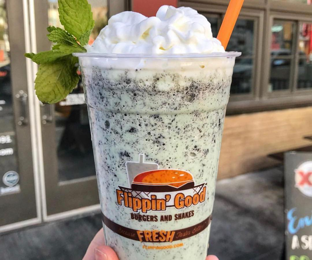A milkshake with whipped cream on top and a straw