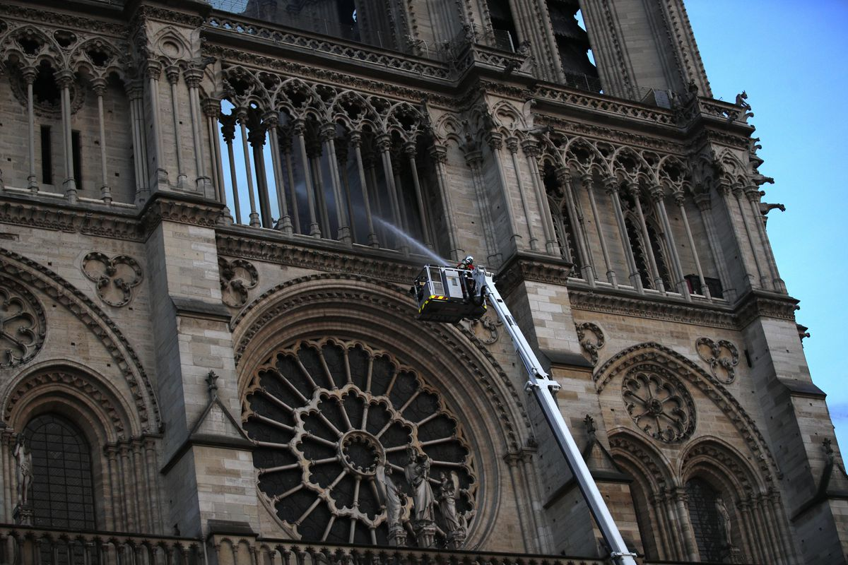 A firefighter sprays a liquid into Notre Dame Cathedral while the monument is burning in Paris, Monday, April 15, 2019. A catastrophic fire engulfed the upper reaches of Paris' soaring Notre Dame Cathedral as it was undergoing renovations Monday, threaten