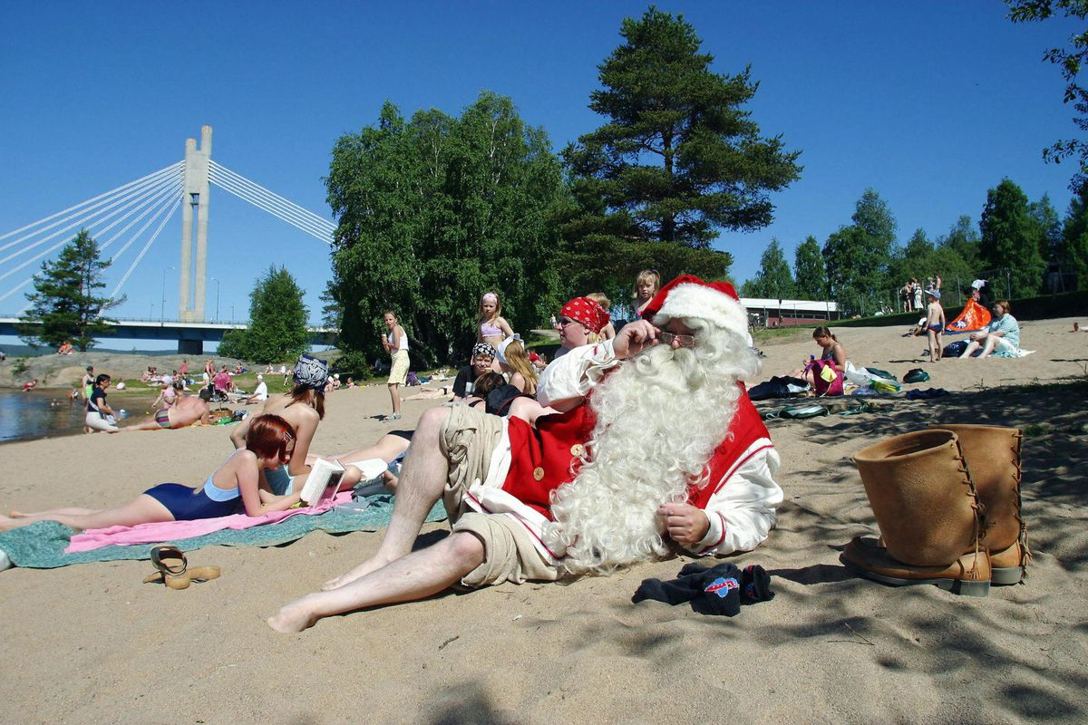 Santa Claus relaxes on the beach on a bright, sunny day.