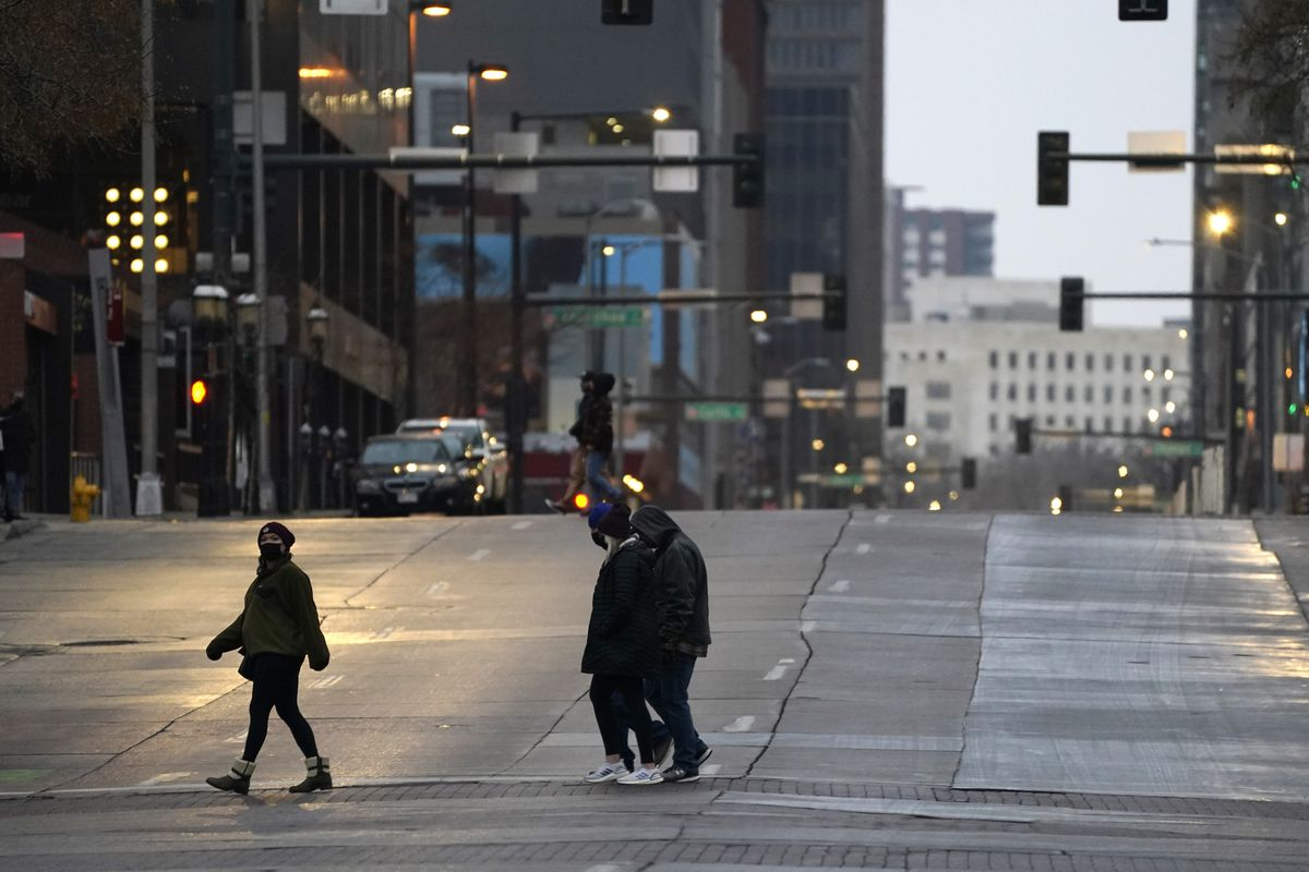 Pedestrians wear masks while crossing an empty road at the intersection of Market Street and 15th Avenue during the evening rush hour Monday, Dec. 28, 2020, in downtown Denver.