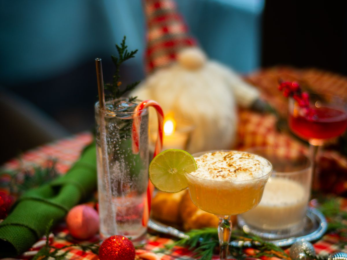 Many holiday cocktails on a table with red and green tablecloth.