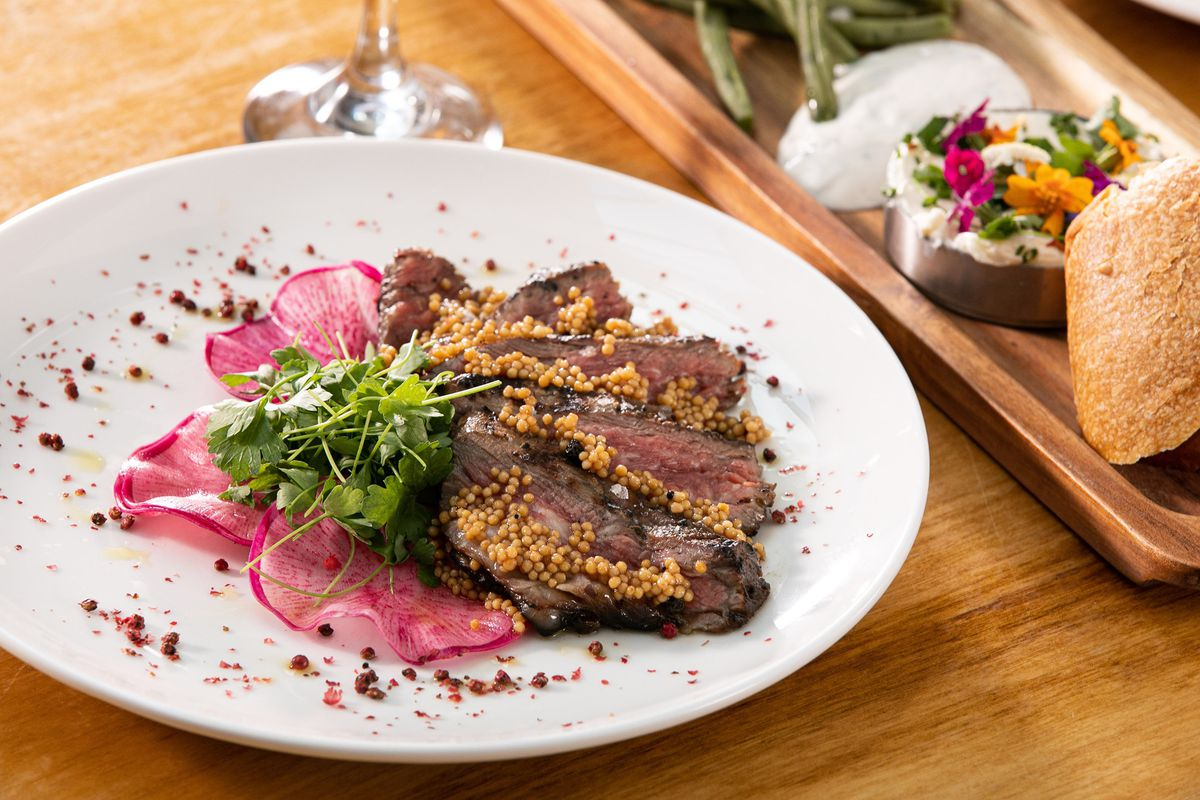 A white plate filled with slices of beef, mustard seeds, and thin-sliced radish.