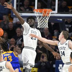 San Jose State guard Seneca Knight (13) shoots as Utah State center Neemias Queta (23) and forward Justin Bean (34) defend during the first half of an NCAA college basketball game Tuesday, Feb. 25, 2020, in Logan, Utah.