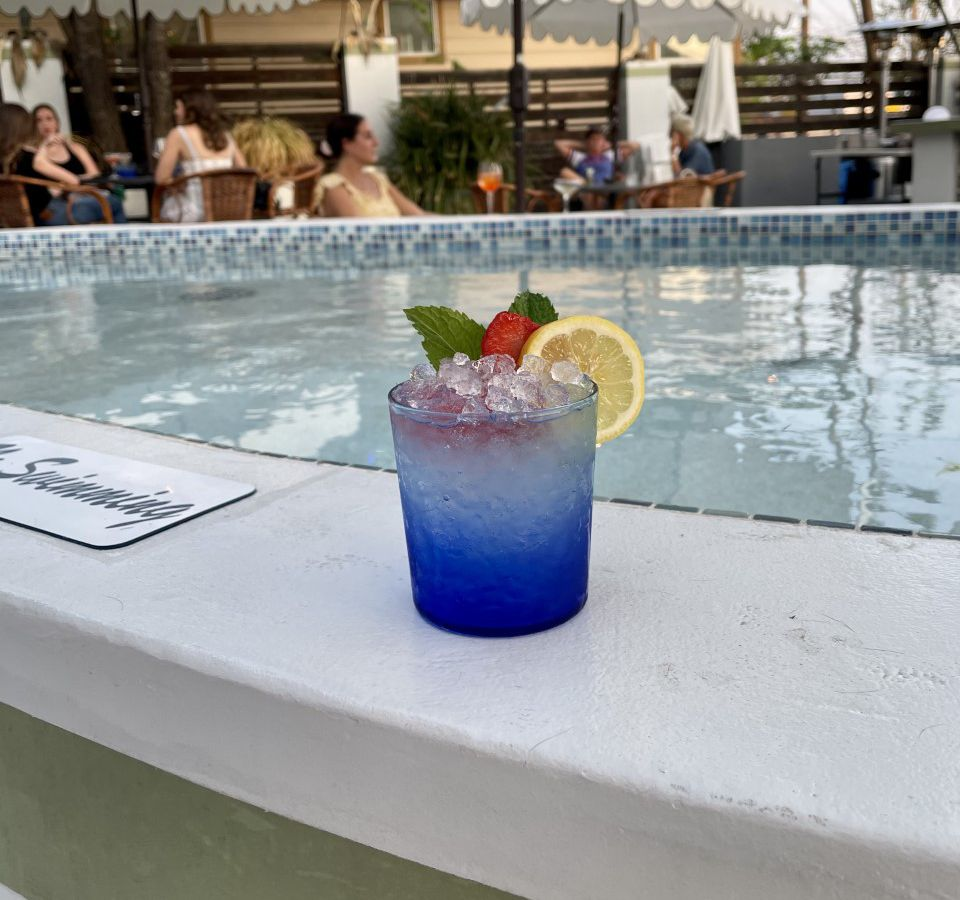 A cocktail in a blue ombre glass sits by a pool with white umbrellas and has a lemon slice and a strawberry on the rim