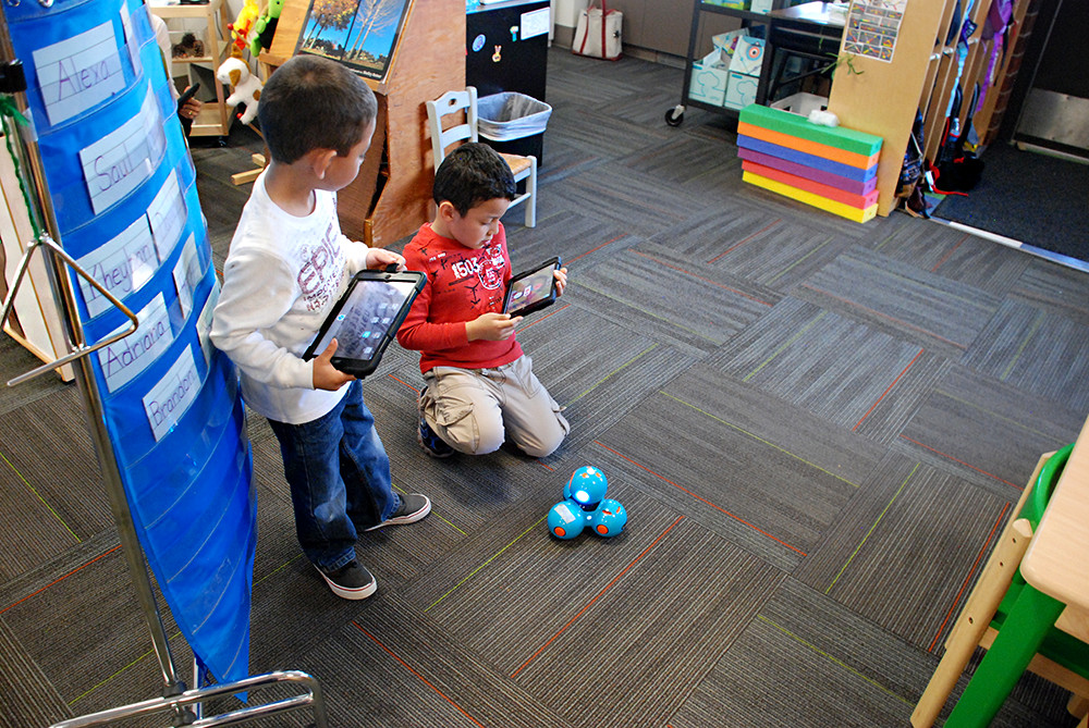 Preschool students at Indian Peaks Elementary School work with Dash the robot.