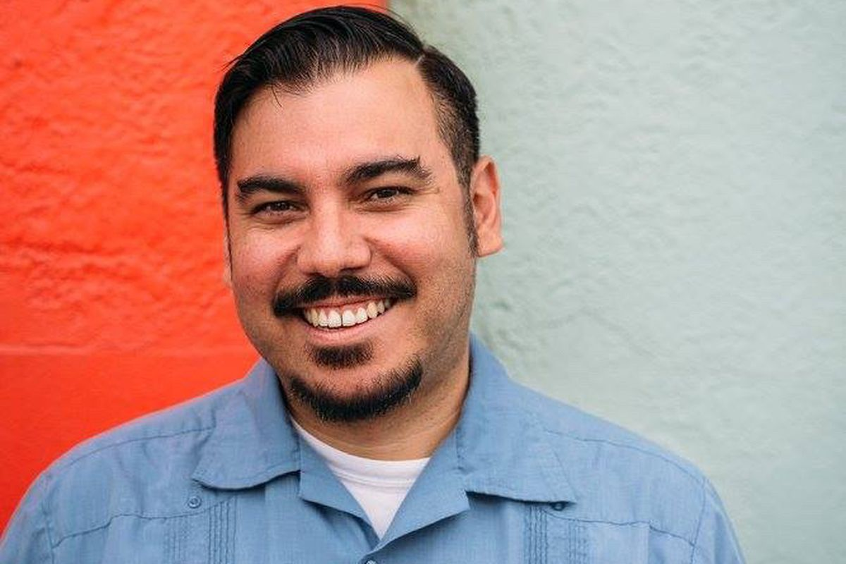 A man with dark short hair and a moustache wearing a blue button-up short over a white shirt standing in front of an orange and light gray wall
