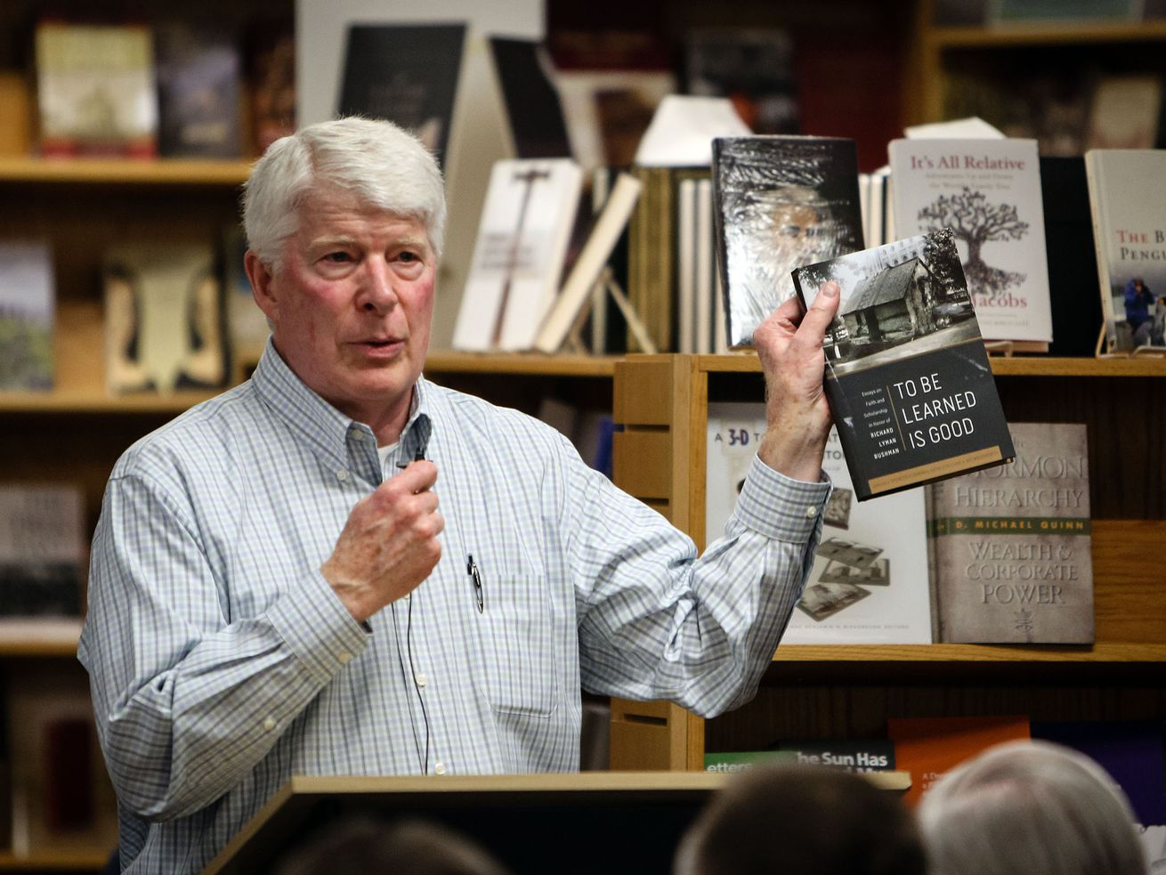 Curt Bench holds a book and speaks to a crowd gathered at his store Benchmark Books before an author's book signing event.