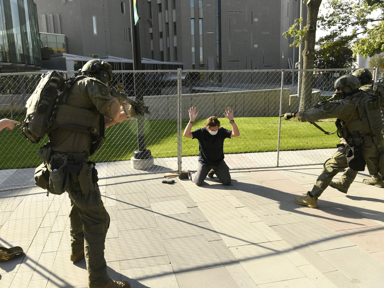 A white man, in a black T-shirt, black jeans, and a white mask, kneels in front of a chain link fence with his hands up. Beside him is a handgun. Three law enforcement officers in military-style body armor, including helmets, surround him, their assault rifles pointed at him. A man in the corner of the photo in a black t-shirt points at the suspect.