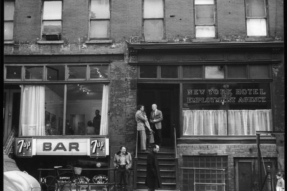 Dutch American artist Willem de Kooning (1904 - 1997) (center, with light hair) speaks with an unidentified couple at the top of a stoop next door to the Tanager Gallery (the storefront above the 'Bar' sign) on 10th Street, New York, New York, April 5, 1959. (Photo by Fred W. McDarrah/Getty Images) *** Local Caption *** Willem de Kooning