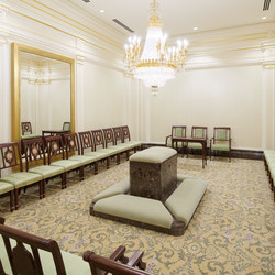 A sealing room in the Mesa Arizona Temple. A replica crystalline chandelier, fluted pilasters and inlaid wood-backed chairs are reminiscent of the Colonial Revival style popular in the 1920s. Here, families are joined together for time and eternity.