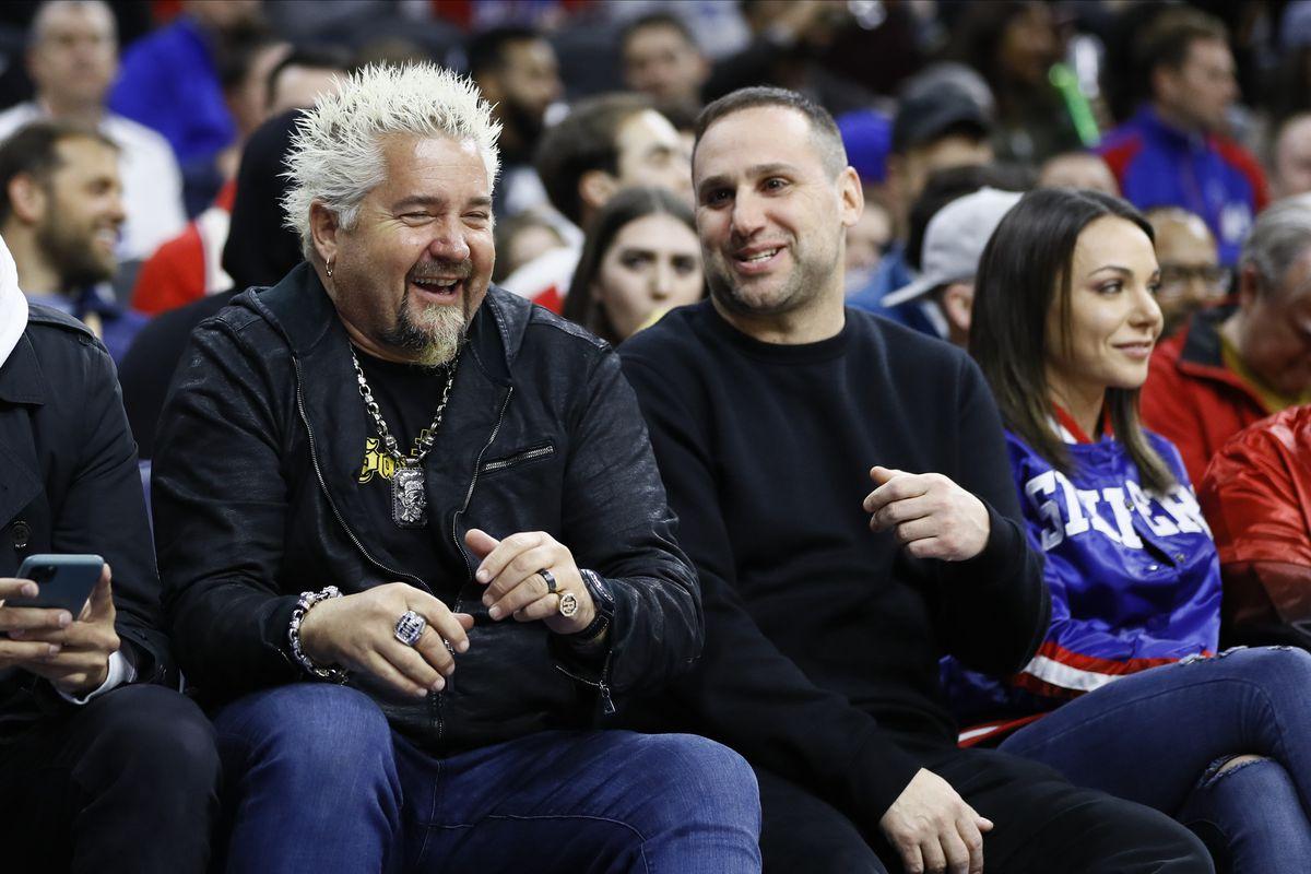 Restauranteur Guy Fieri, left, and Philadelphia 76ers' Michael Rubin laugh during an NBA basketball game between the Philadelphia 76ers and the Detroit Pistons, Wednesday, March 11, 2020, in Philadelphia. (AP Photo/Matt Slocum)