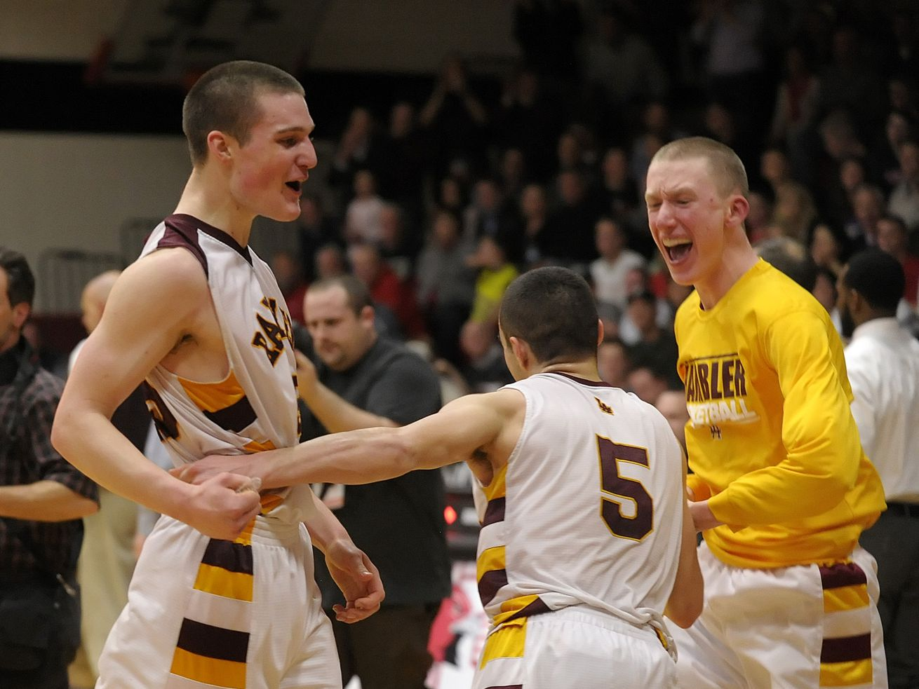 Loyola's Jack Morrissey celebrates with James Clarke (5) after the final buzzer. Loyola defeated Maine South 42-37 to win the Class 4A Maine South Sectional in 2014.