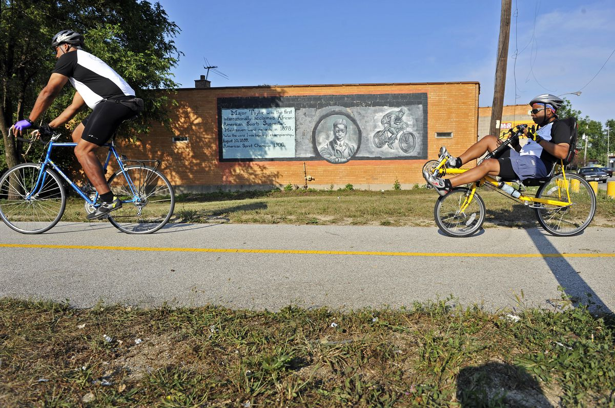 Peter Taylor (left) and Ed Dixon from the Major Taylor Cycling Club ride past a mural of late champion cyclist Major Taylor on the Far South Side.