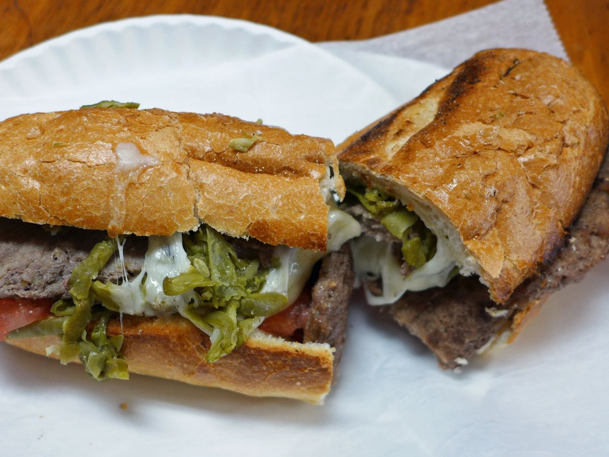 A cut hero sandwich with roast beef, white melted cheese, and green beans sticking haphazardly out.
