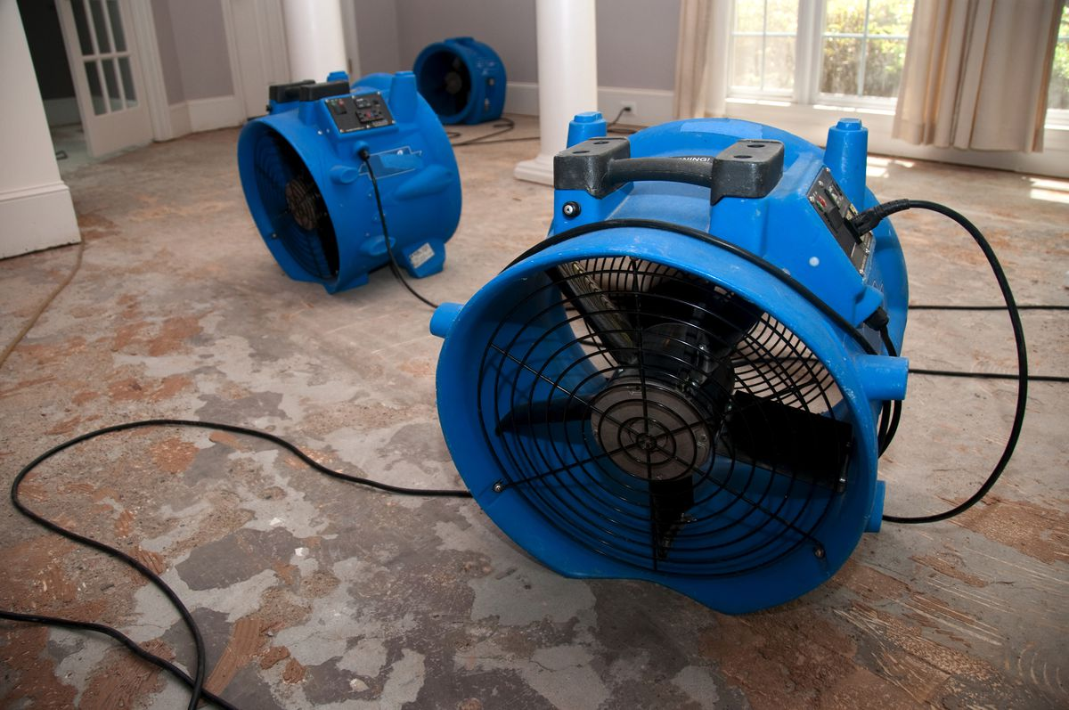 Two blue industrial sized fans sitting on a subfloor.