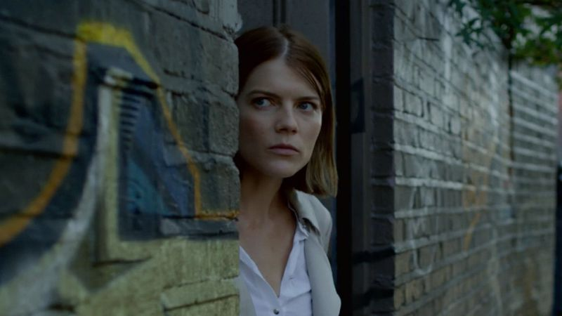 Emma Greenwell as Myfanwy peers around a doorway in The Rook