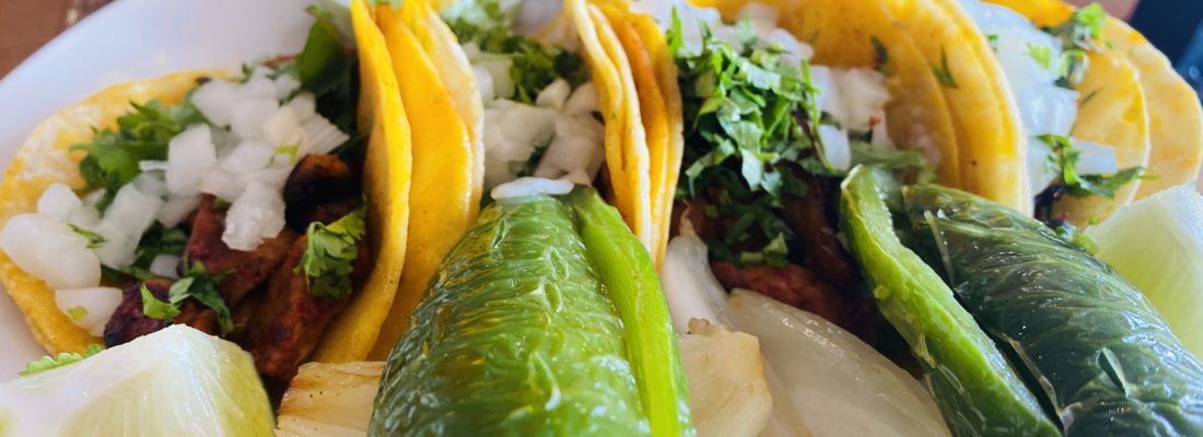 An extreme close up of yellow corn tortilla tacos and a wrinkled jalapeño