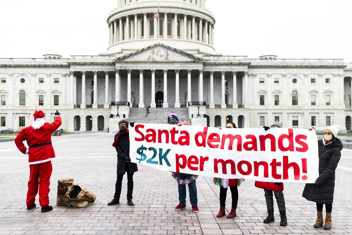 """A person dressed as Santa accompanies people carrying a banner that reads, """"Santa demands $2k per month!"""" outside the Capitol building."""